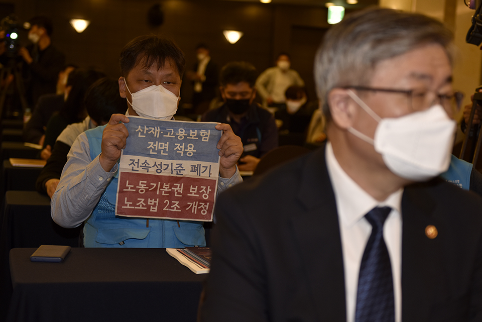 대리운전 노동자가 이재갑 고용노동부 장관 뒤에서 '노조법 2조 개정' 피켓을 들어 보이고 있다. ⓒ 김한주 기자